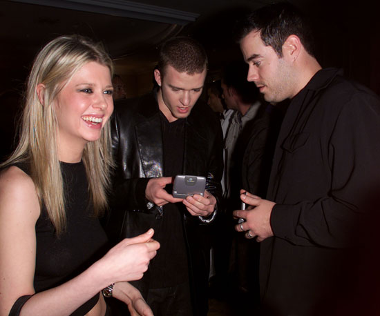 Carson Daly and Justin Timberlake check their cells as Tara Reid laughed in 2001.
