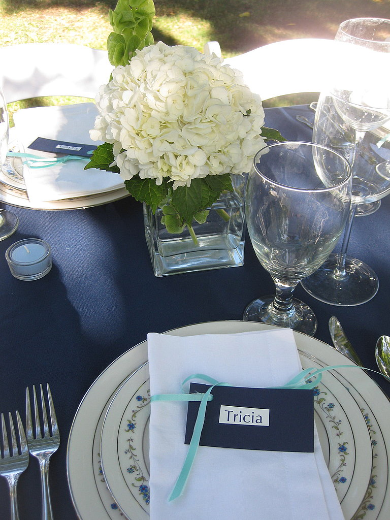 I created a seating chart and didn't allow couples to sit next to each other. Then, I printed everyone's name on white cardstock and mounted this on blue cardstock. I punched a hole in the name card, slid a turquoise ribbon through it, and wrapped the ribbon around each napkin.