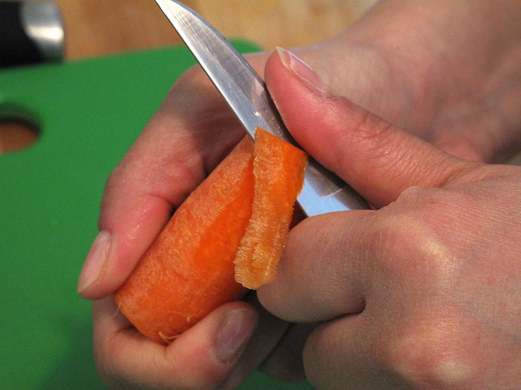 Hold the vegetable between your thumb and forefinger, carefully peeling it toward you in as tapered a shape as possible.