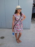 The ideal Spring ensemble — floral dress, fedora, gladiator sandals, crossbody bag, and water.