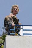 Eva Herzigova hung out on a balcony looking luxe in a strapless print dress and fur jacket.