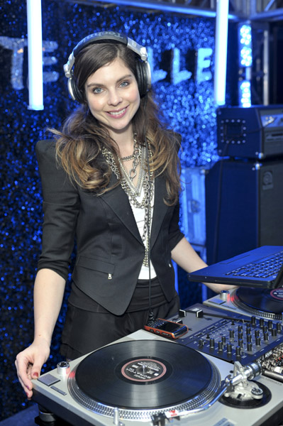 DJ Daisy O'Dell spinning jams in a fashionable black getup. Cool headphones!