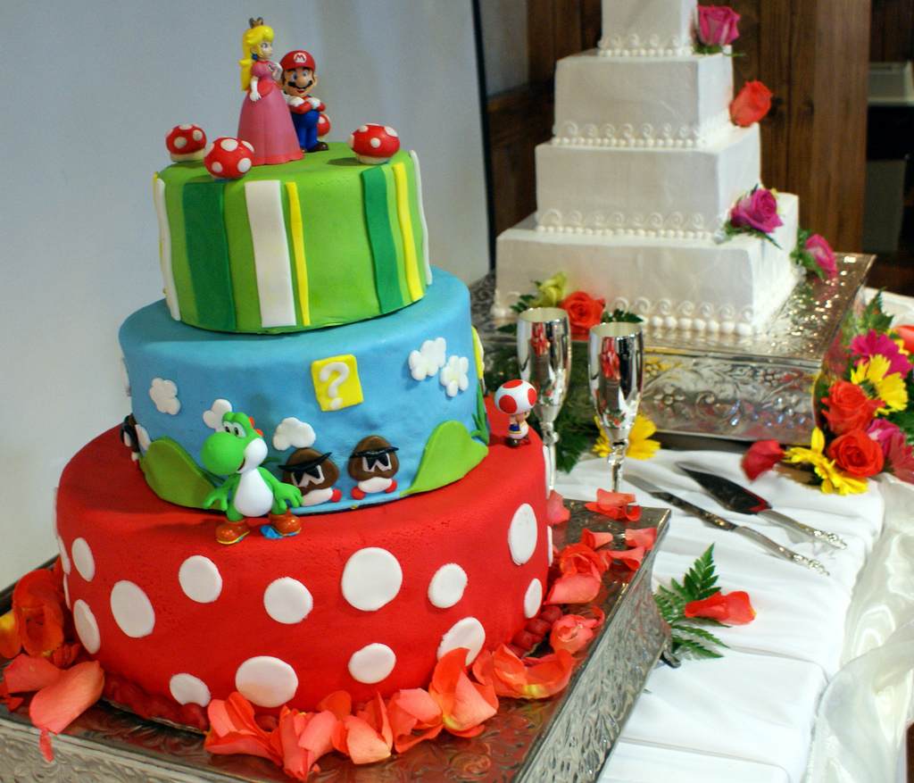 The geeky groom's cake beside a wedding cake is a quirky touch without sacrificing the traditional white cake.  Source: Flickr User HeroicLife
