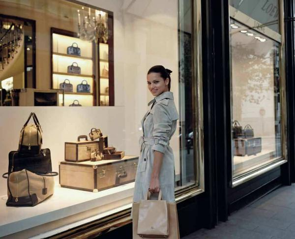 Adriana looks quite happy while window shopping in a classic trench.