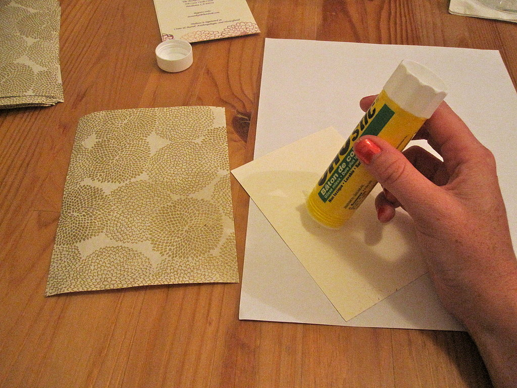 Turn the text card over and cover the whole surface with glue. Paste in the middle of the decorative paper. Repeat with all of the text cards.