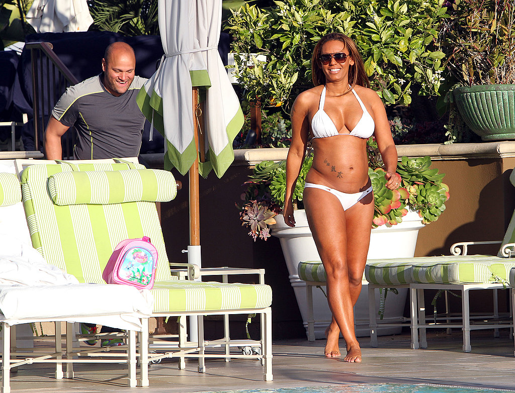 Former Spice Girl Melanie Brown slipped into a white bikini to hang out at the pool with her husband.