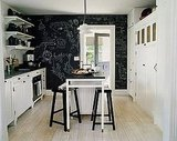 The kitchen in this Shelter Island fisherman's cottage fits in with the rest of the house's black and white color scheme, and I love the whimsical chalkboard wall.