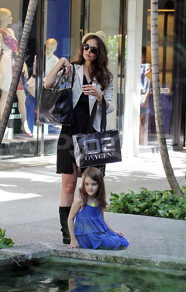 Katie Holmes and Suri Cruise sat by a fountain.