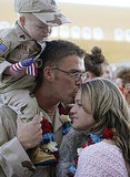 In 2004, Army Sgt. Cody Smith kisses his wife, Kelsie, while his nephew Brandon looks on in Salt Lake City, UT.