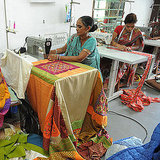 Two Indian women sew traditional quilts.