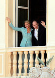 Waving to onlookers, Princess Charlene of Monaco and Prince Albert II of Monaco head out to the balcony.