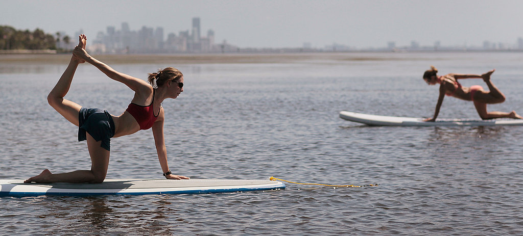 Two women pose during paddleboard yoga session.