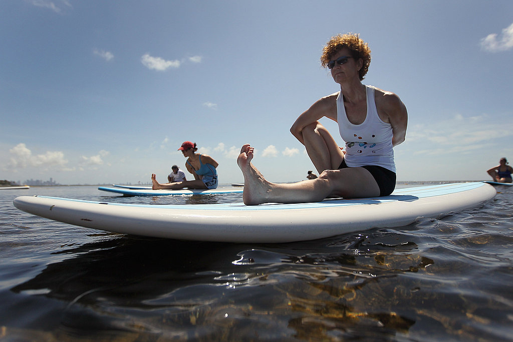A woman participates in a paddleboard yoga class on the water in Miami.