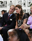 Prince William leans in for a word with Kate during a dance performance during their tour of the Inner City Arts.