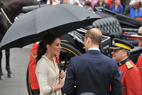 Kate Middleton held an umbrella as she spoke with Prince William.