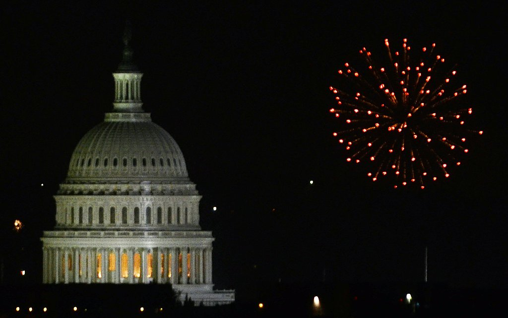 Bright bursts go off behind the US Capitol building in Washington DC.