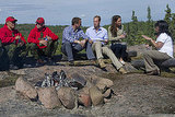 Kate Middleton and Prince William sat around a bonfire.