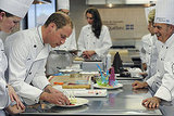 Dressed in a chef's coat, Prince William plates a dish at a cooking class in Montreal, while his wife, Kate, wears a matching one in the background.