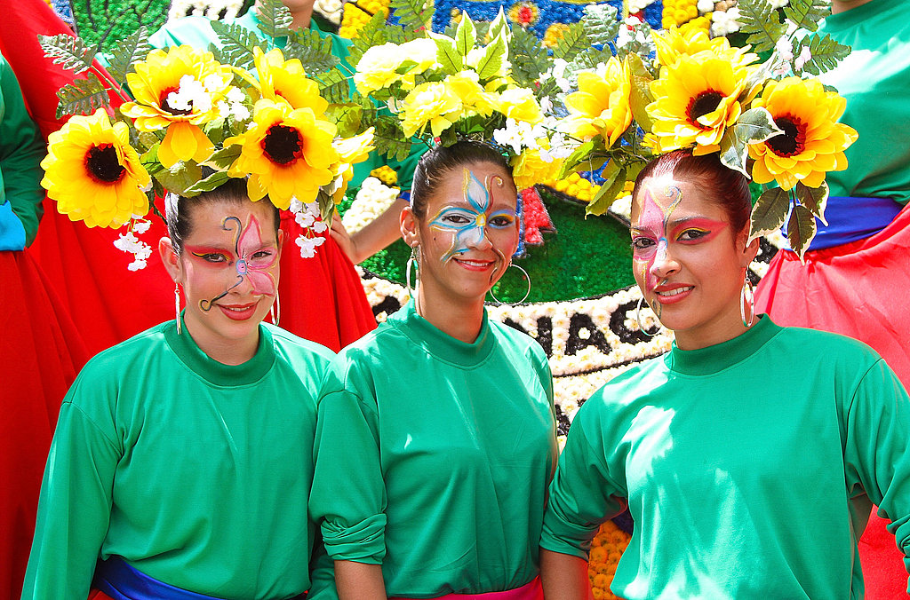 Three women don sunflowers on their head during the Feria De Flores (Flower Fair).