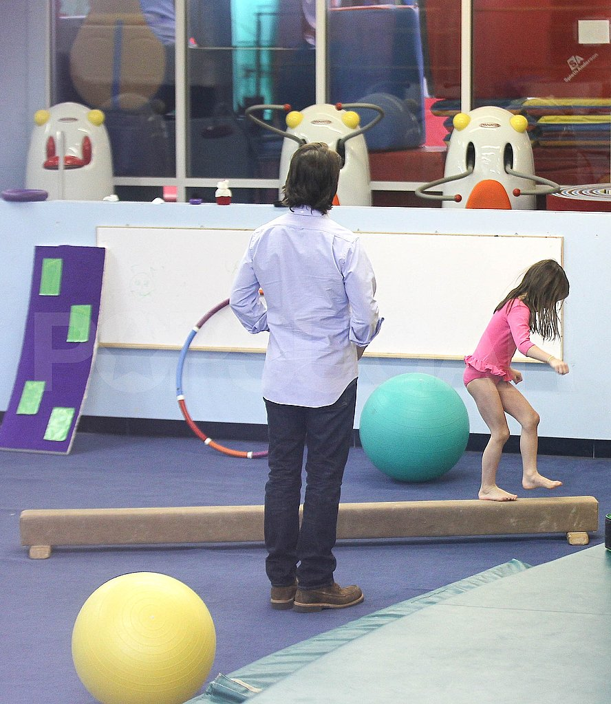 Tom Cruise watches Suri Cruise do gymnastics.