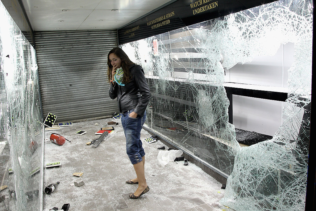 A girl examines the destructive aftermath of looters in a pawn shop during the London riots.