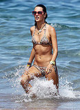 Alessandra Ambrosio wears a bikini and sunglasses.