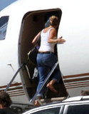Jennifer Aniston boards a private plane in a tank and jeans.