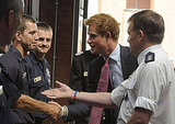 Prince Harry shakes the hands of firefighters.