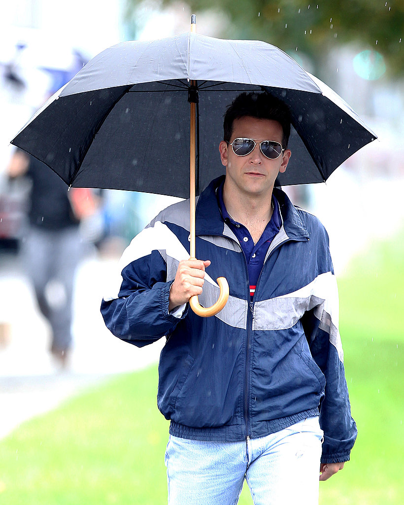 Bradley Cooper kept dry under an umbrella.