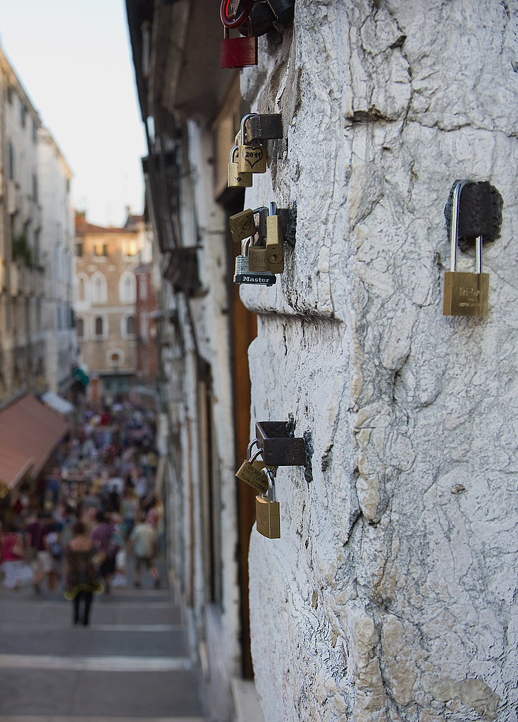 Love padlocks adorn a wall on Rialto Bridge in Venice, Italy.