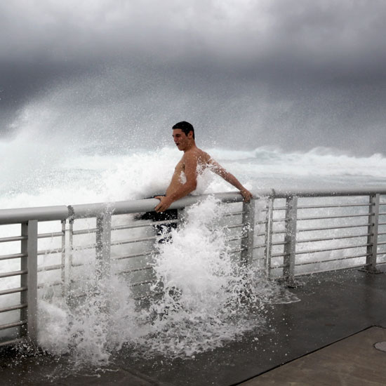A daredevil hangs off a pier at Boynton Beach in Florida as Hurricane Irene moves over the Bahamas and approaches the US.