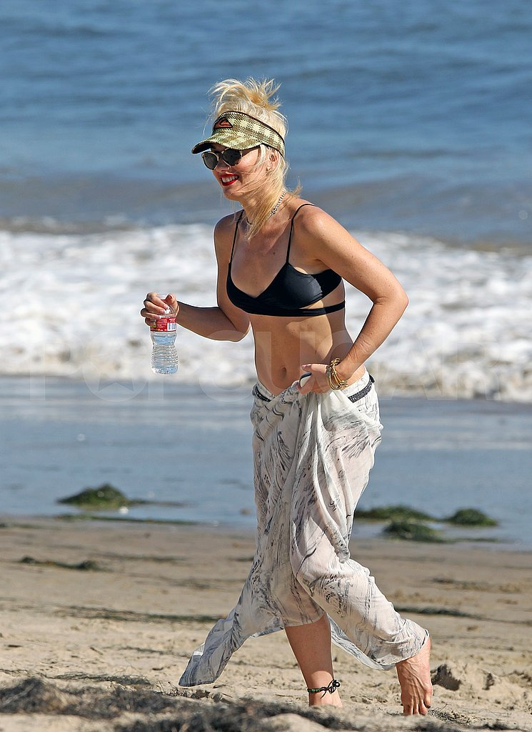 Gwen Stefani runs on the beach in a bikini top with a water.