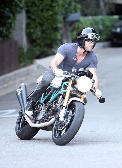 Ryan Reynolds on a motorcycle outside of Sandra Bullock's house.
