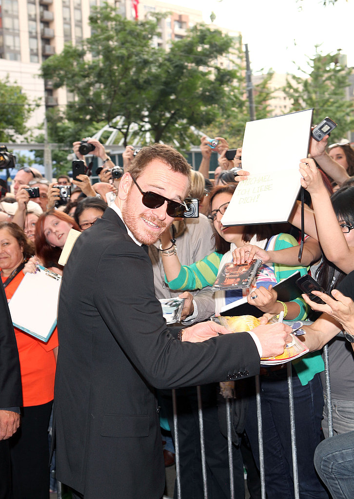 Michael Fassbender signs autographs.