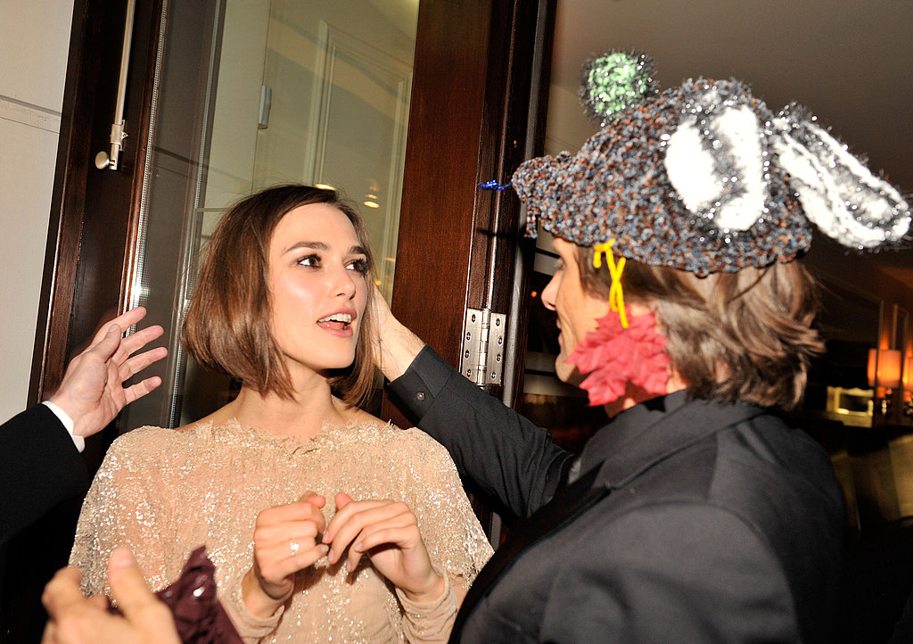 Keira Knightley admires Viggo Mortensen's hat during a party.