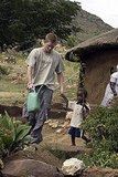 In 2004, Harry holds hands with a young boy at the Mants'ase children's home in Lesotho.