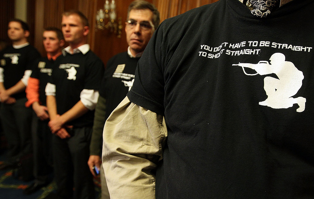 "Activists wear shirts reading, ""You don't have to be straight to shoot straight"" during a news conference on Dec. 15, 2010."