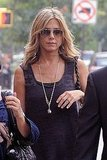 Jennifer Aniston accessorized with a long gold chain and aviator sunglasses.