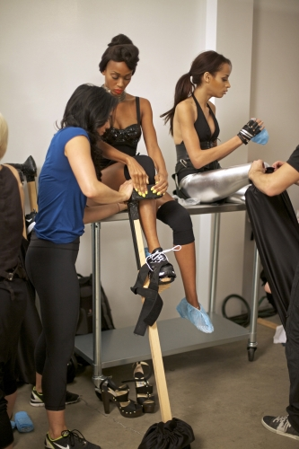 Assistants strapped Camille and Isis into their stilts.  Photos courtesy of The CW