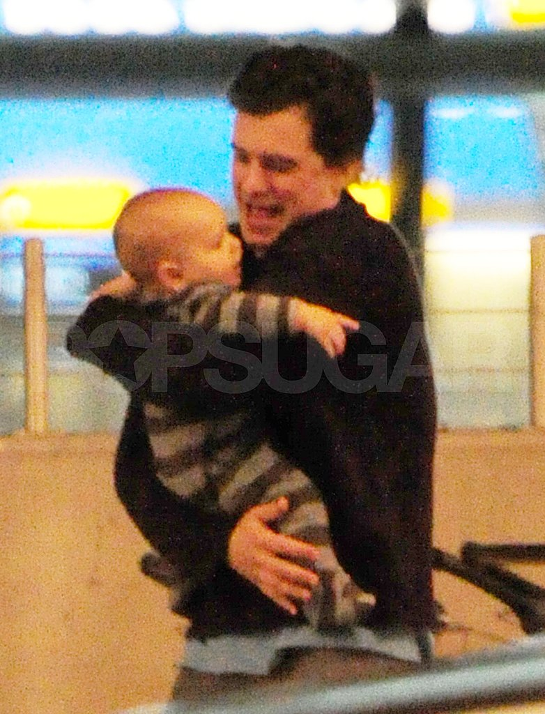 Orlando Bloom cradles his son in London.