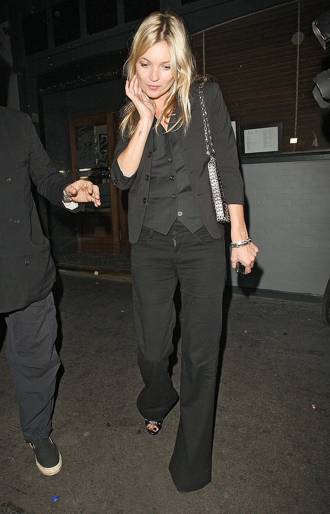 Kate Moss pushed her hair back.