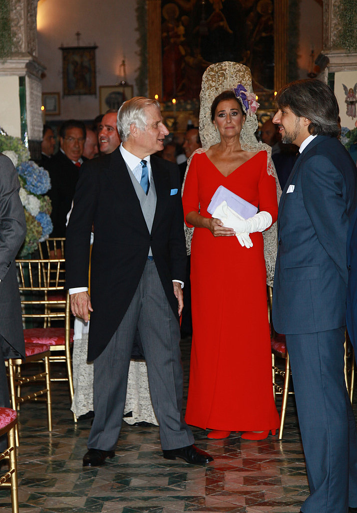 Cayetana's matron of honor, Carmen Tello, walks down the aisle in red.