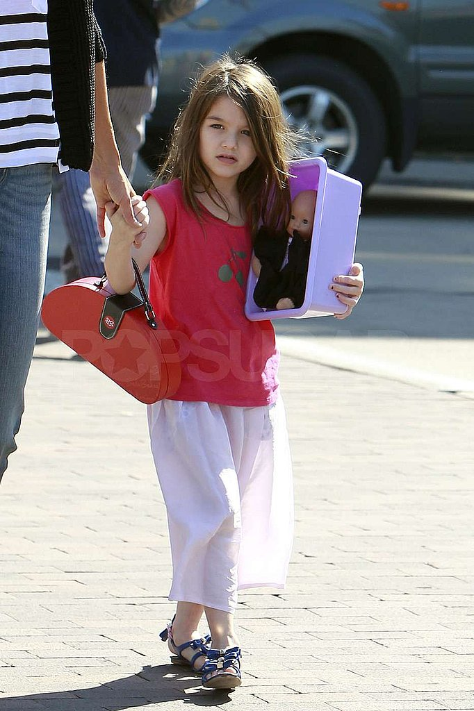 Suri Cruise carried a baby doll in a container.