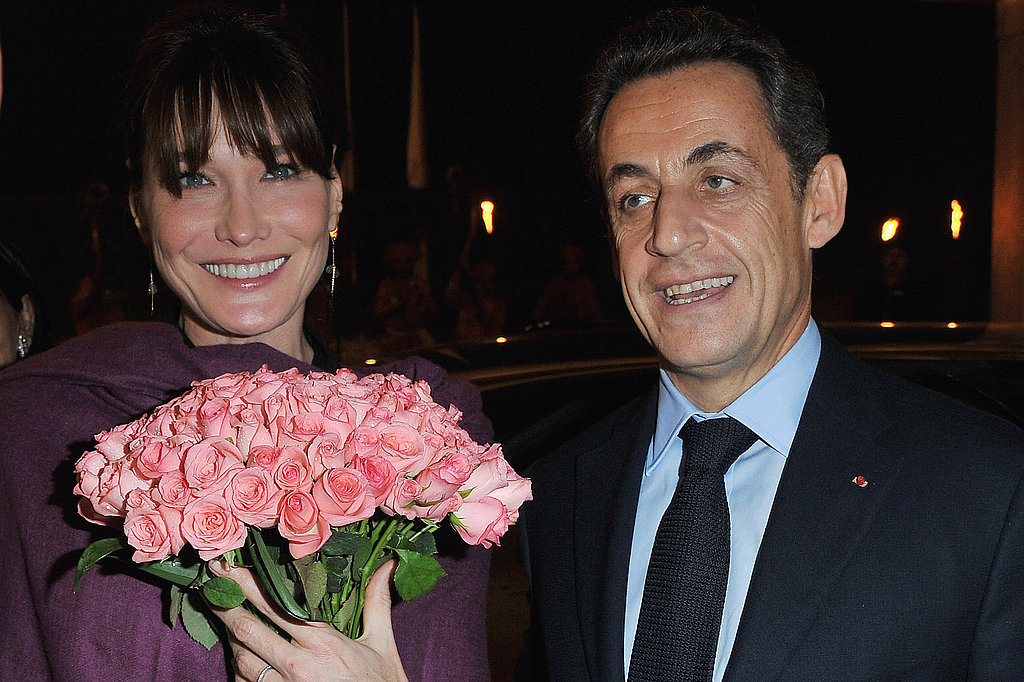 Carla Bruni holds roses as she and Nicolas Sarkozy arrive in India last December.