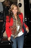 Beyoncé Knowles in a red jacket and leopard scarf.