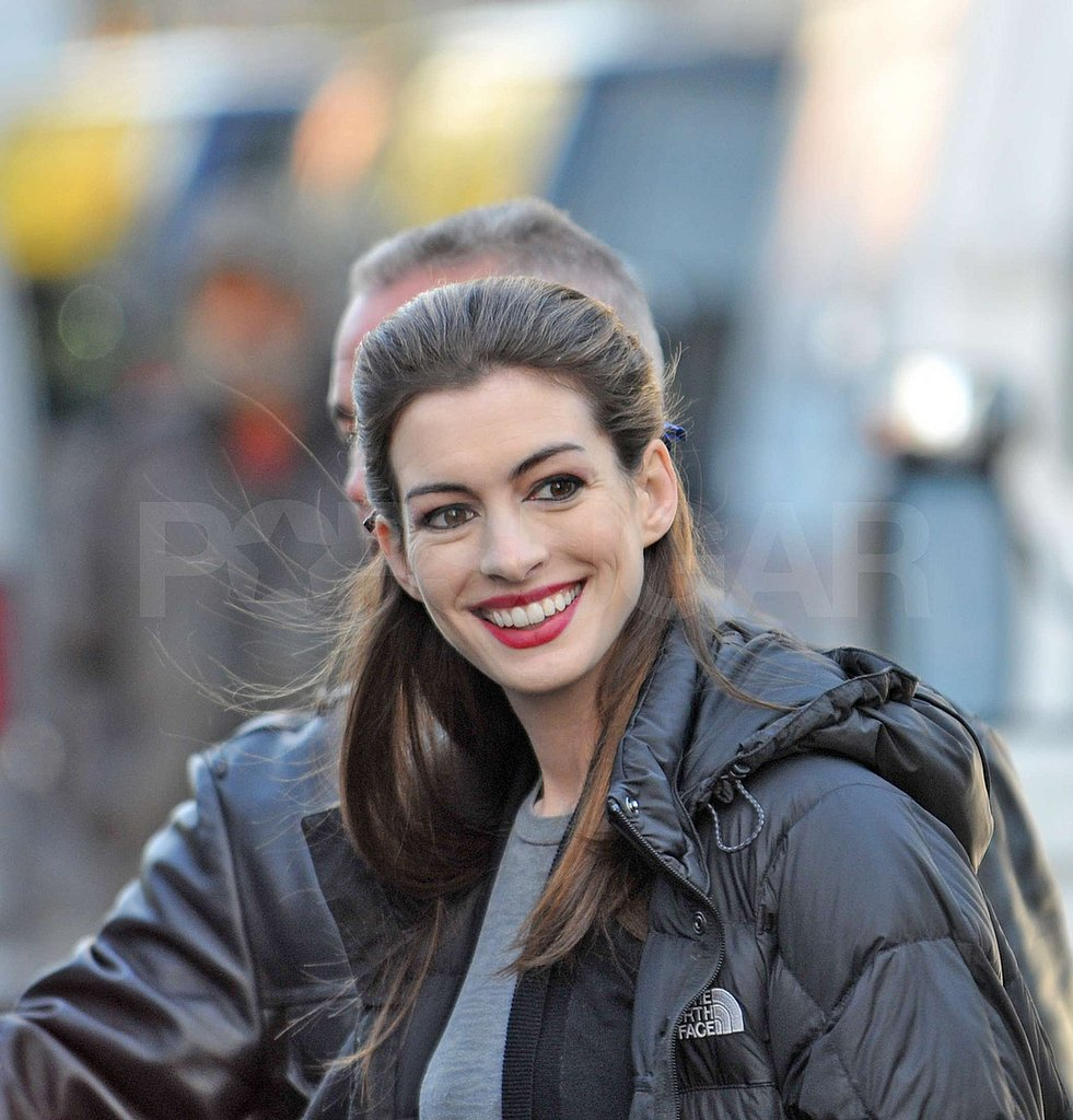 Anne Hathaway flashed a smile as she was escorted to the set.