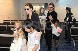 Angelina Jolie and Brad Pitt both wore sunglasses while their kids carried toys through the airport in Tokyo.