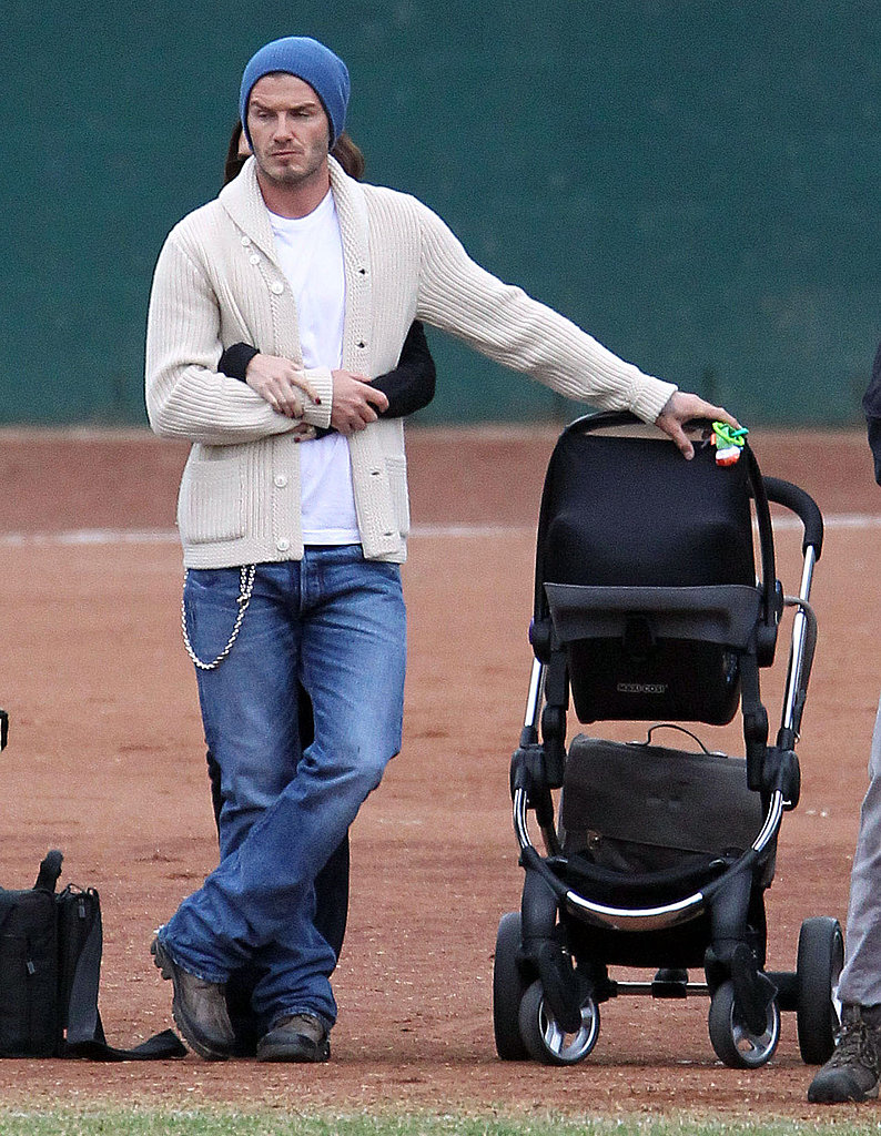 Victoria Beckham put her arms around David, who rested on Harper's stroller.