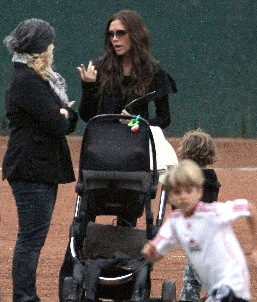 Victoria Beckham pushed baby Harper, while Romeo Beckham ran around at his soccer game.