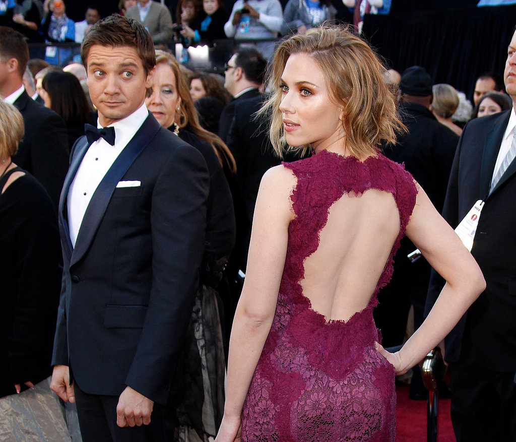 Scarlett Johansson posed on the red carpet at the 2011 Oscars while a dazed Jeremy Renner looked on.